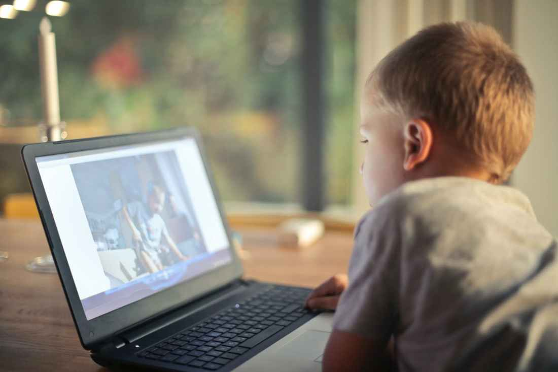 A boy looks at a video on a laptop. There is a danger of too much passive learning when kids do virtual school. It can worsen reading and learning challenges at home.