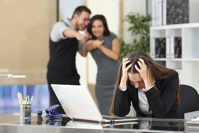 A woman working in an office sits in front of her computer, holding her head in her hands as two coworkers stand behind her and point and laugh at her. Dyslexia anxiety in the workplace can cause irrational fears such as the one depicted in this picture.