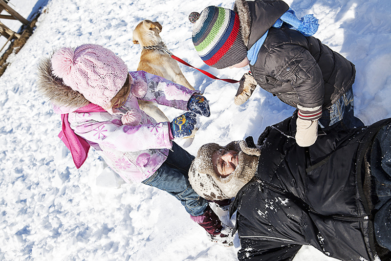 A father plays with his two young children - a boy and a girl - in the snow. They are all wearing snow clothes. A yellow dog is nearby. Part of practicing self-care for families involves spending time away from screens and if possible, outdoors.