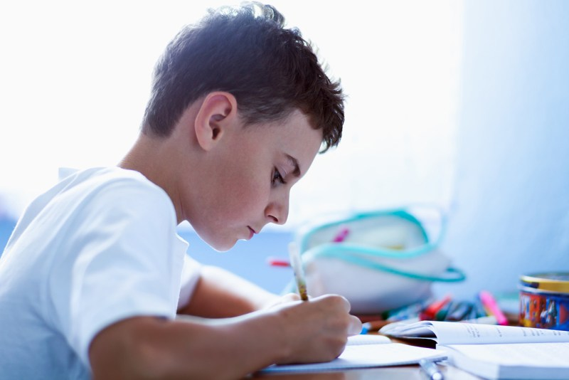 A dark-haired boy wearing a white shirt sits at a desk doing homework. Helping your struggling reader after the third grade is difficult but not impossible.