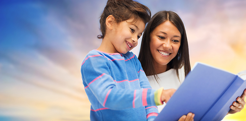 A mom reads with her child against a sunset background. Helping your struggling reader after the third grade is difficult but not impossible.