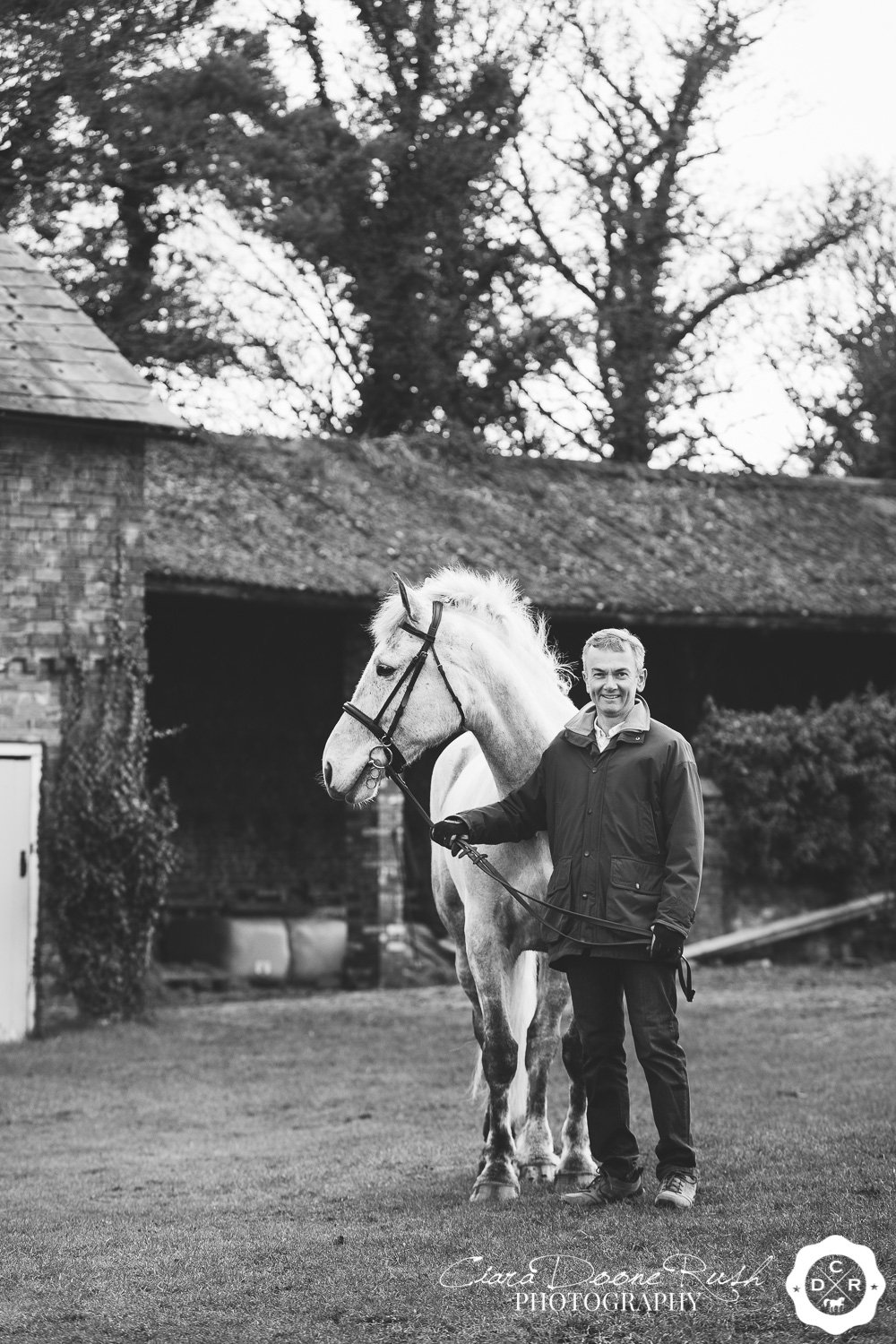 A man holding his horse in a stable yard