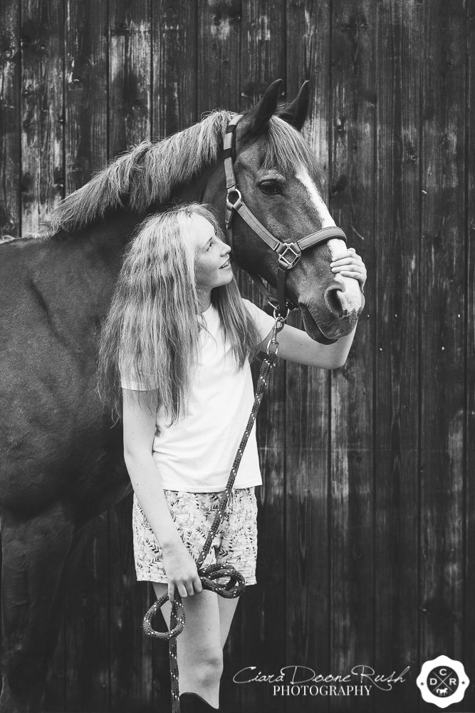 A girl and her pony by the stables