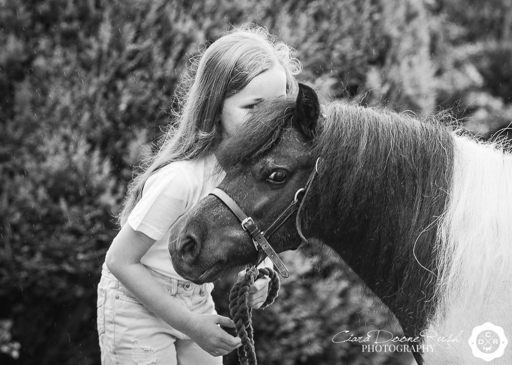 A little girl kissing her pony
