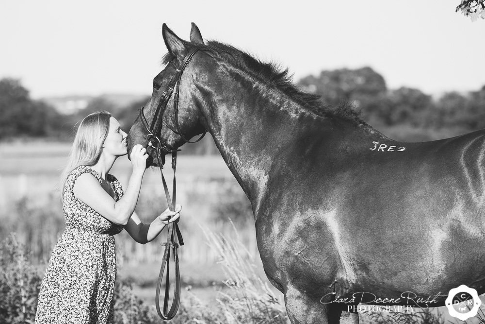 black and white photo of a woman kissing her horses nose