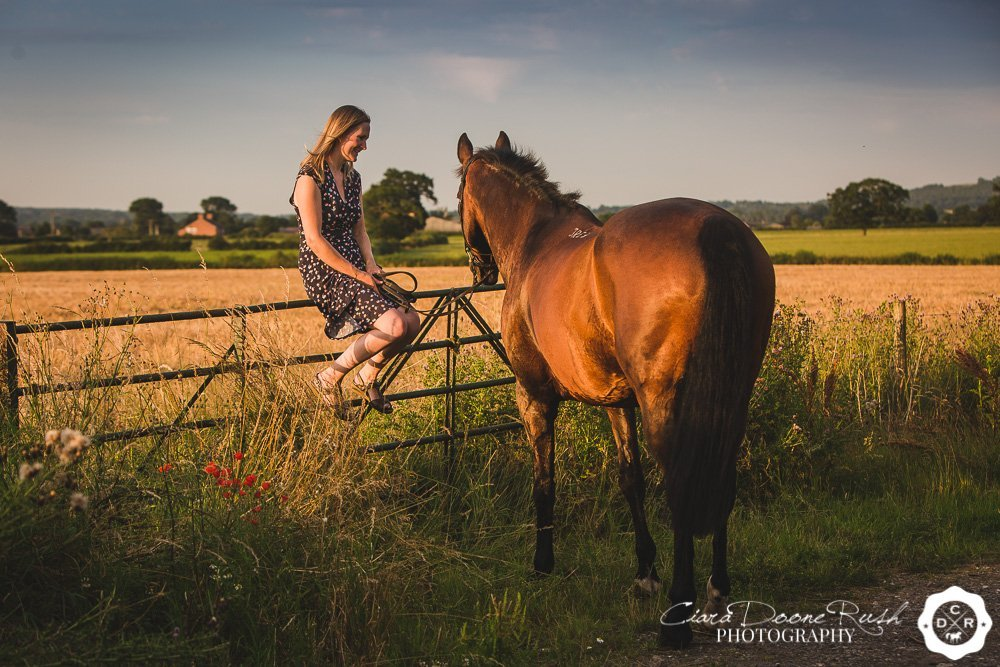 a woman sitting on a gate during a photo shoot with her horse