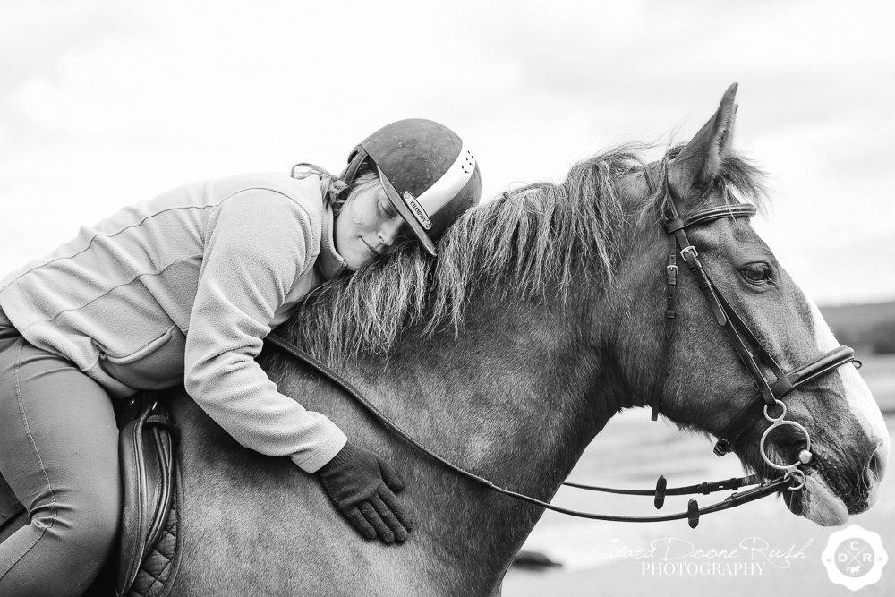 a girl hugging her horse