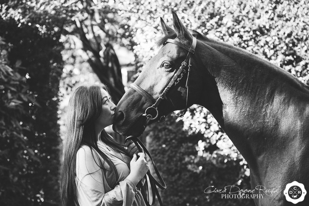 a rider kissing her horse