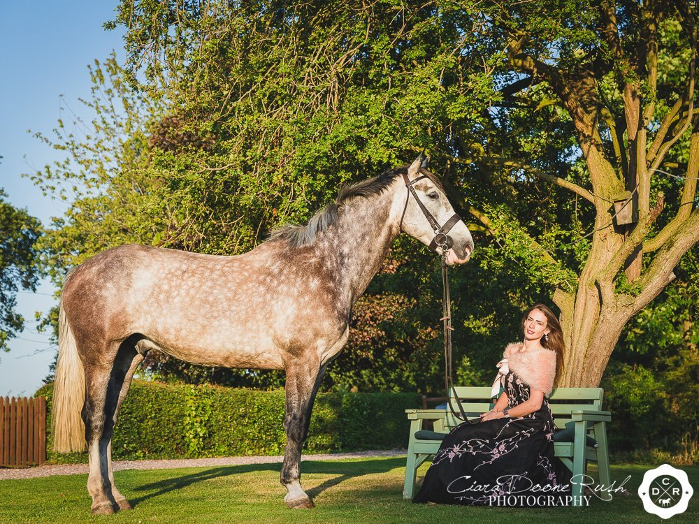 a woman in an evening dress with her horse