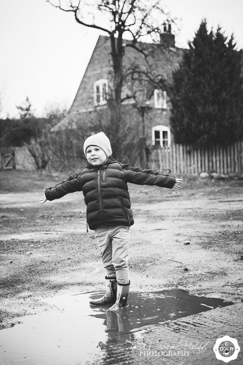 a little boy jumping in puddles