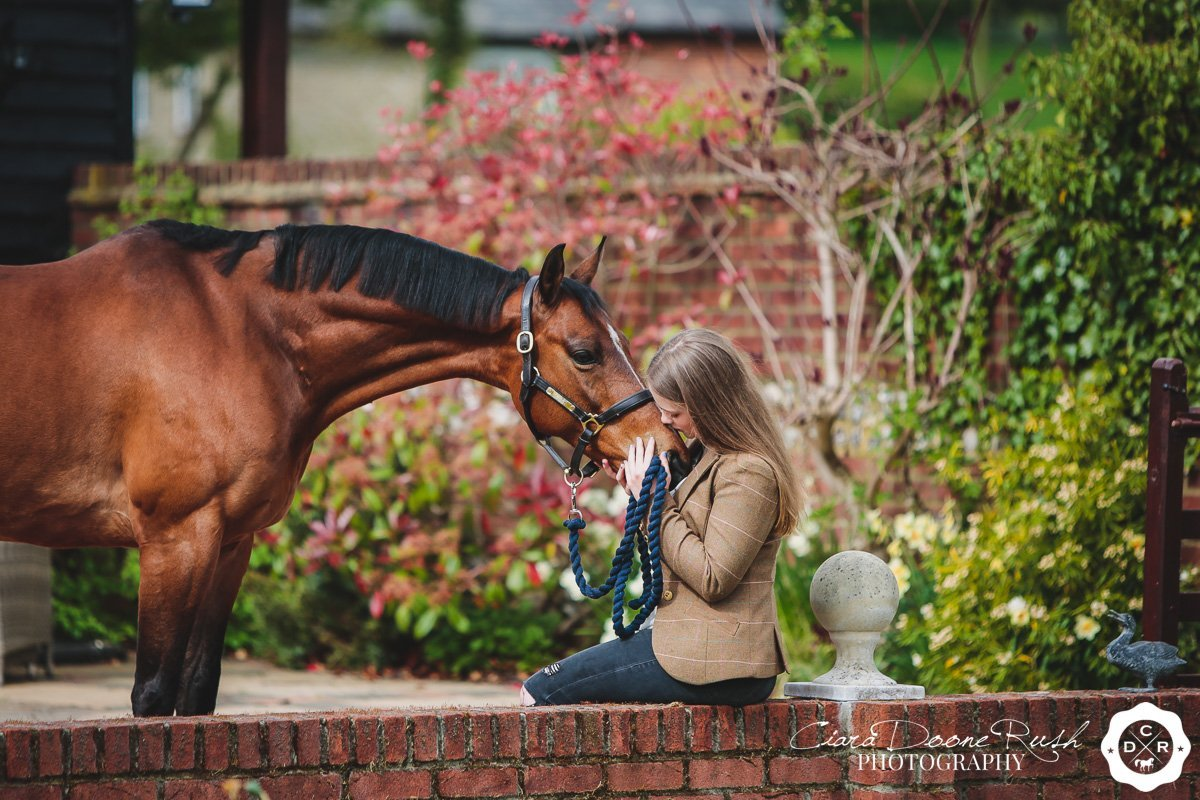a girl giving her pony kisses on a photo shoot