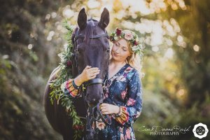 a woman and her black horse with evening sunshine