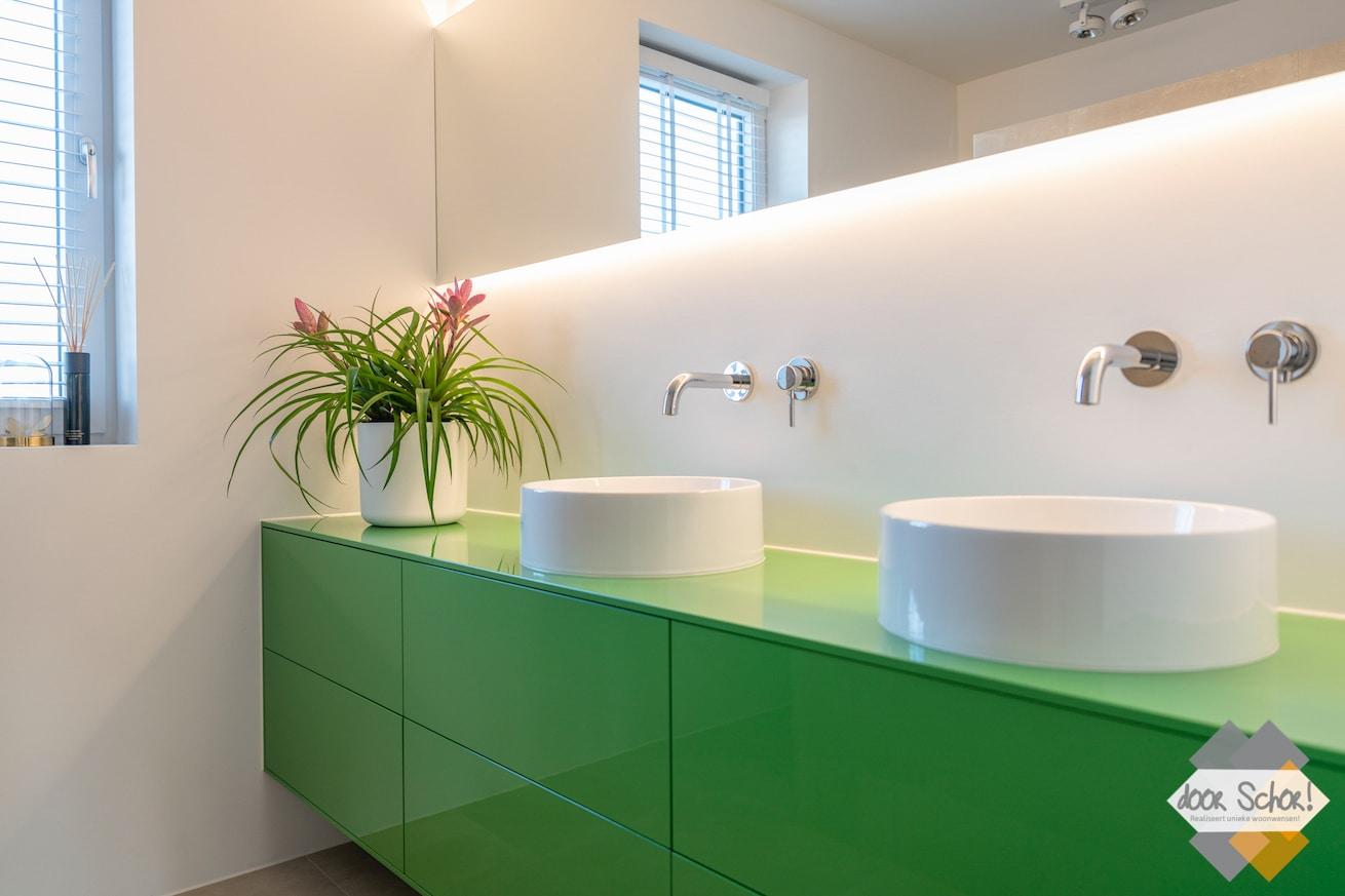 Een knal groen maatwerk meubel voor in de badkamer met twee witte kommen