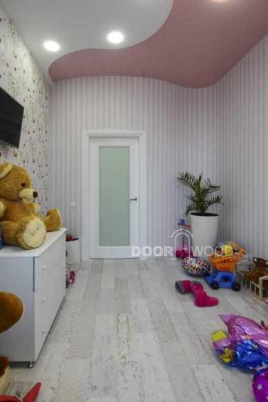 Белая межкомнатная дверь из ясеня со стеклом Сатин в детской комнате.