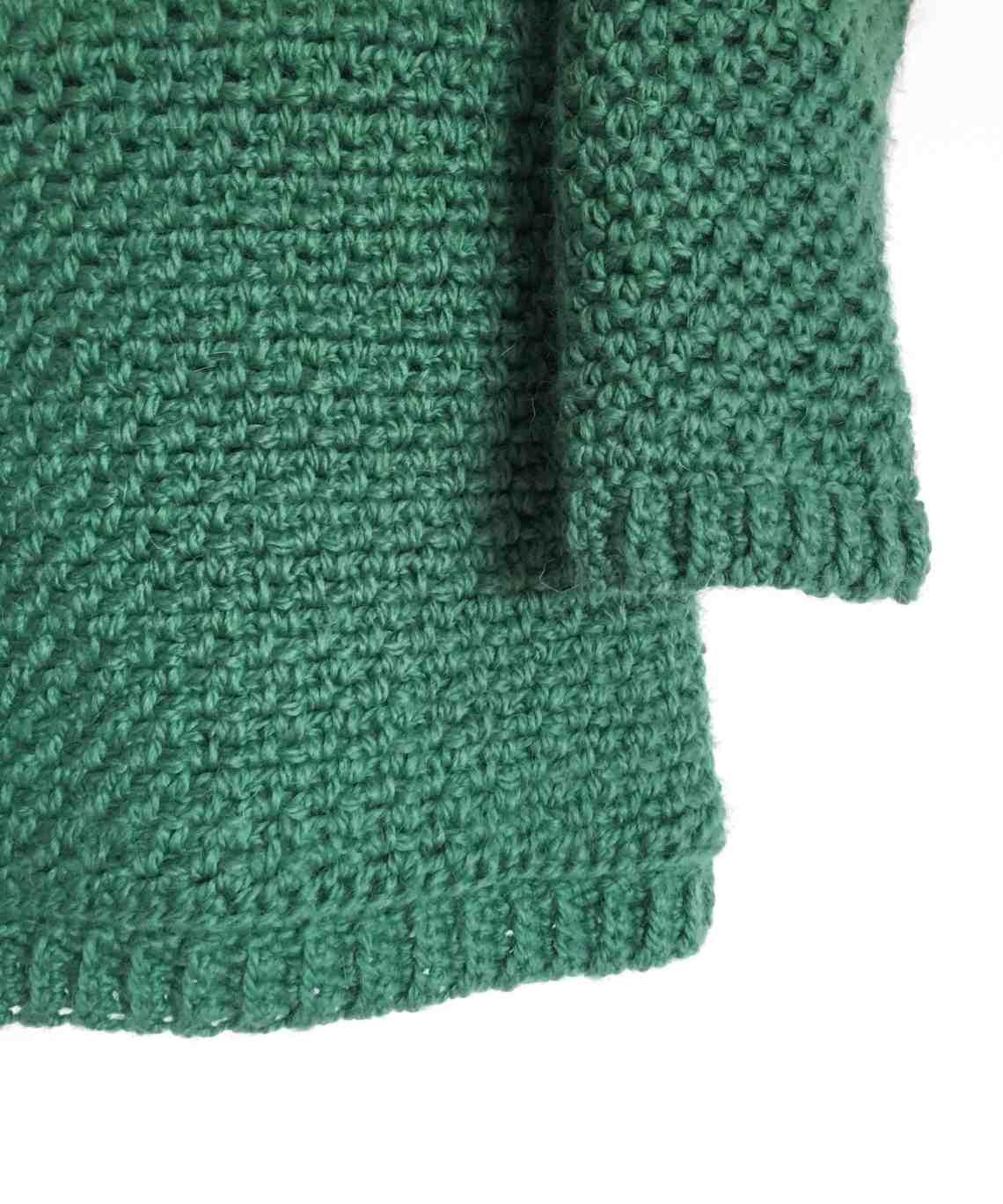 Corner of green crochet moss stitch sweater hanging on white wall