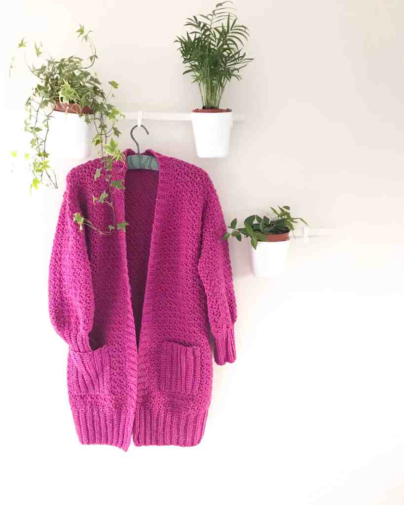 Everyday hugs crochet cardigan hanging with houseplants