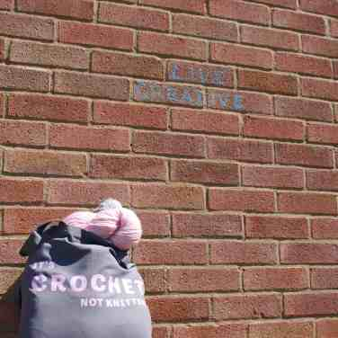 Grey slogan It's crochet not knitting tote bag full of yarn with live creative wall behind