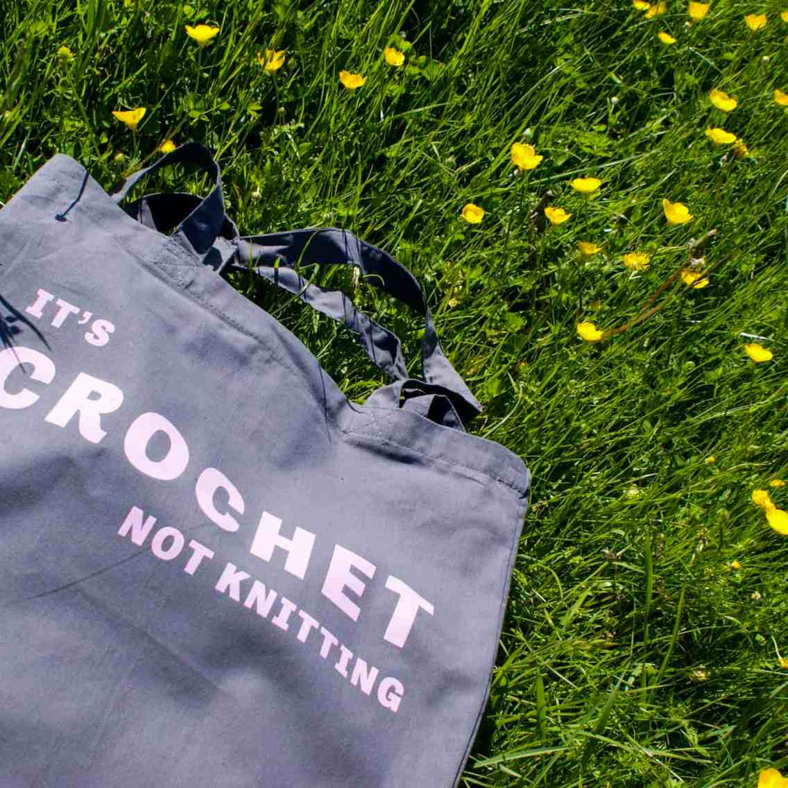 It's crochet not knitting tote bag in grey cotton with blue ink hanging out in the meadow
