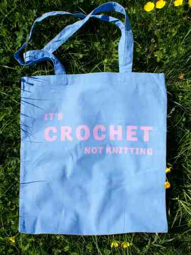 It's crochet not knitting blue cotton tote bag with pink ink