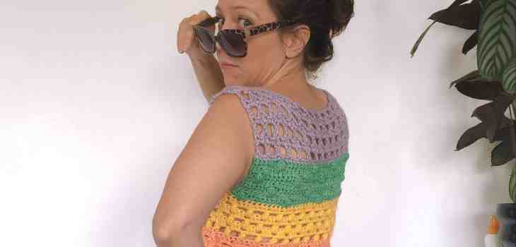 Girl in summer rainbow crochet top wearing sunnies looking over her shoulder