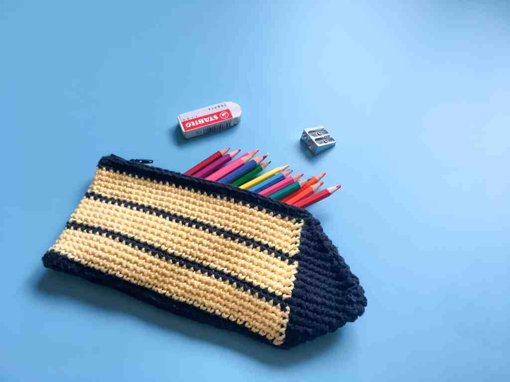 crochet yellow and black stripy pencil case with coloured pencils rubber sharpner