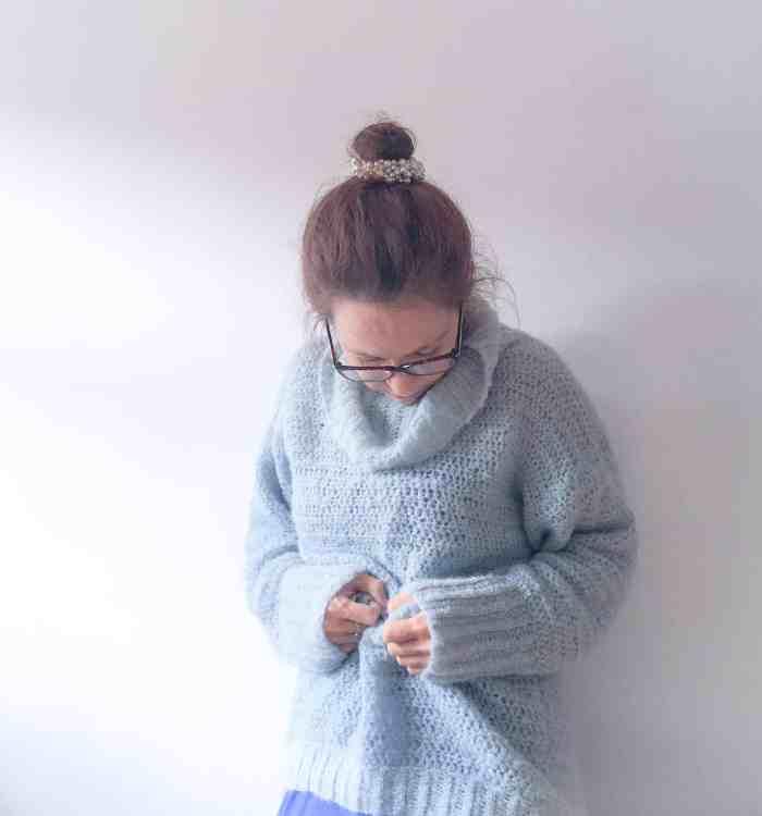 Woman in blue cosy crochet alpaca silk roll neck sweater
