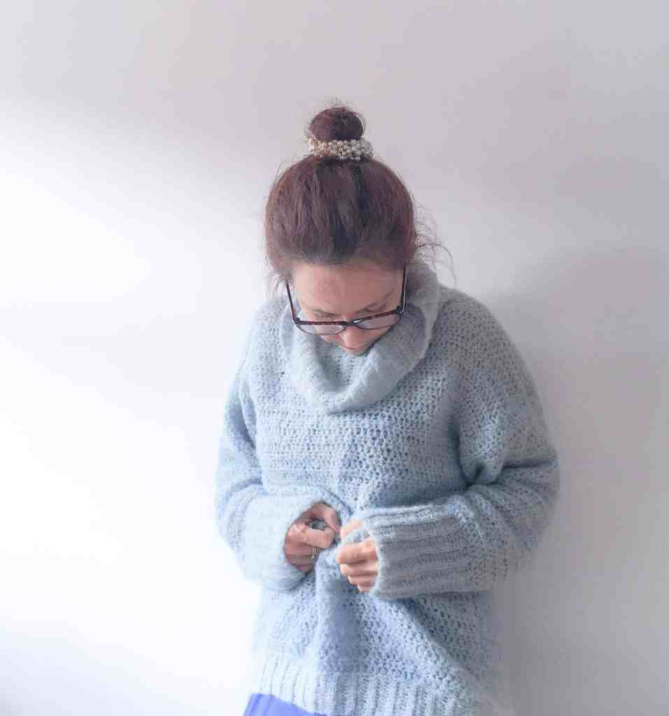 Woman in blue cosy crochet alpaca silk roll neck sweater