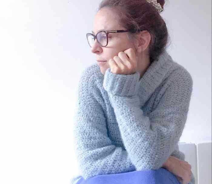 Woman in blue cosy crochet alpaca silk roll neck sweater thinking