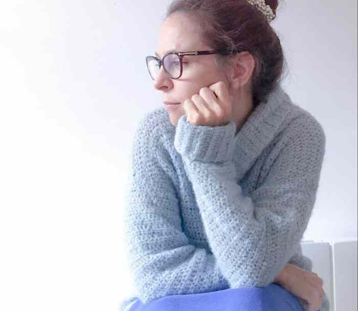 Woman in blue cosy crochet alpaca silk roll neck sweater thinking