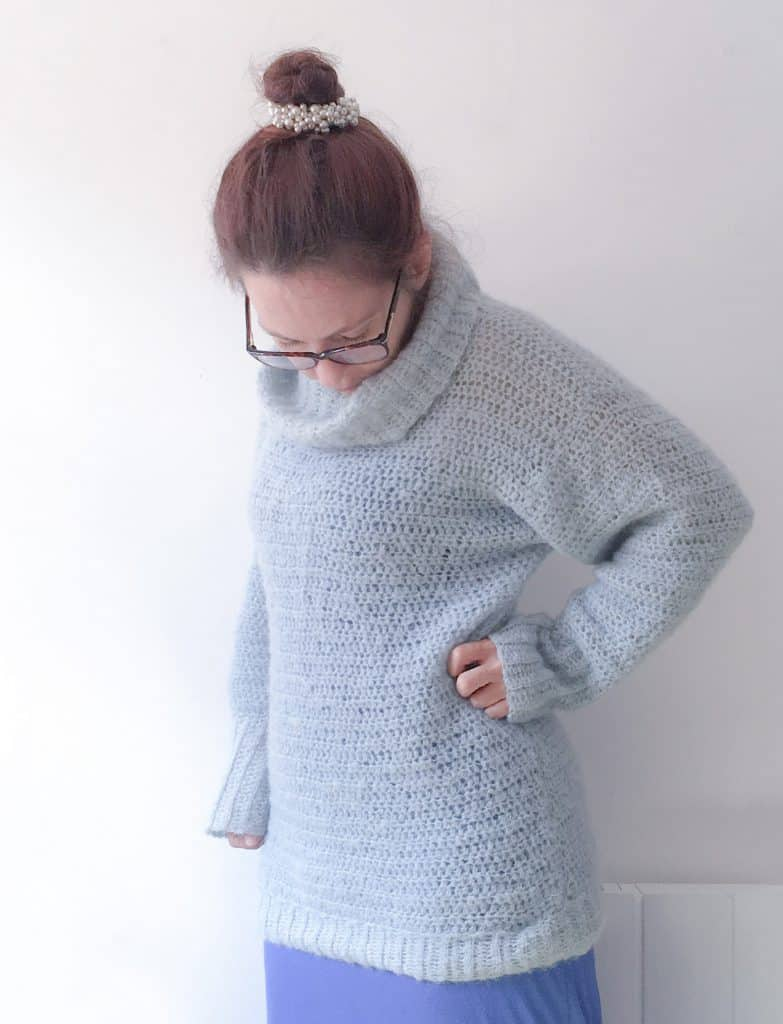 Woman with hand on hip in blue cosy crochet alpaca silk roll neck sweater