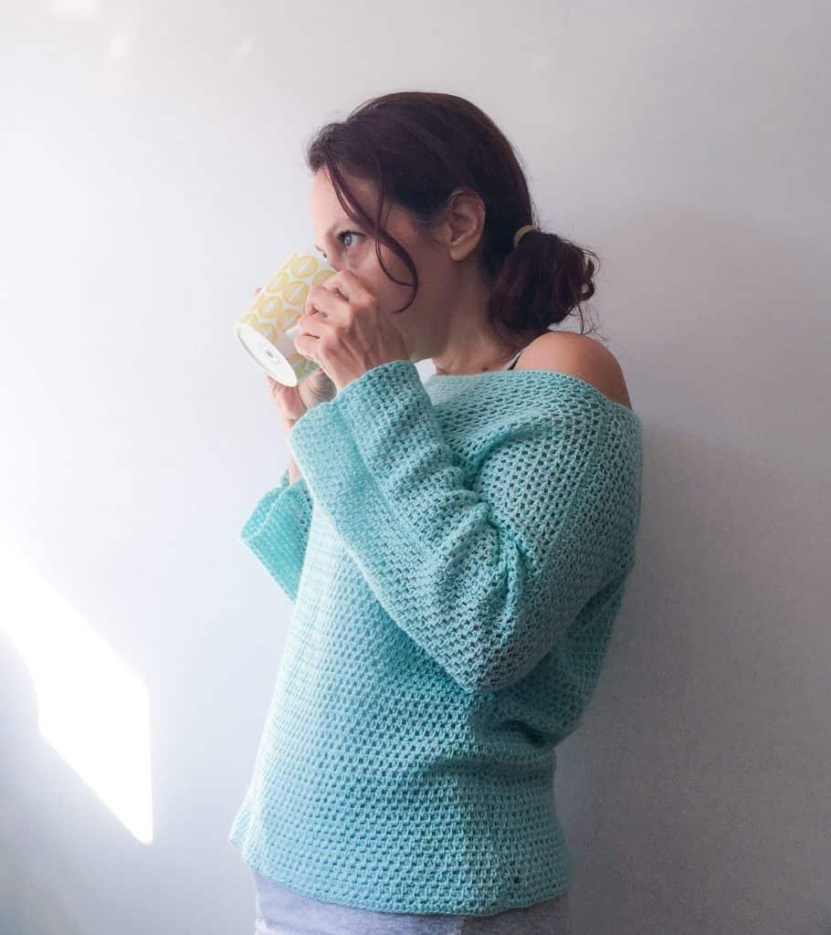 Woman drinking tea in turquoise crochet sweater