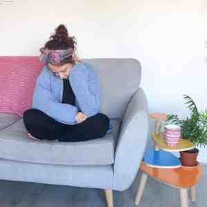 Girl on sofa wearing crochet cardigan