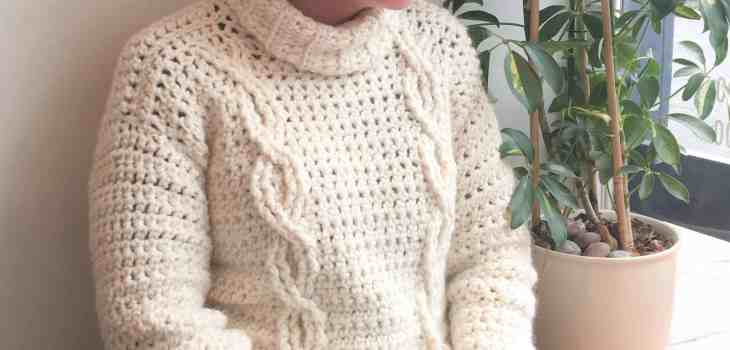 Girl looking out window wearing cabled crochet sweater