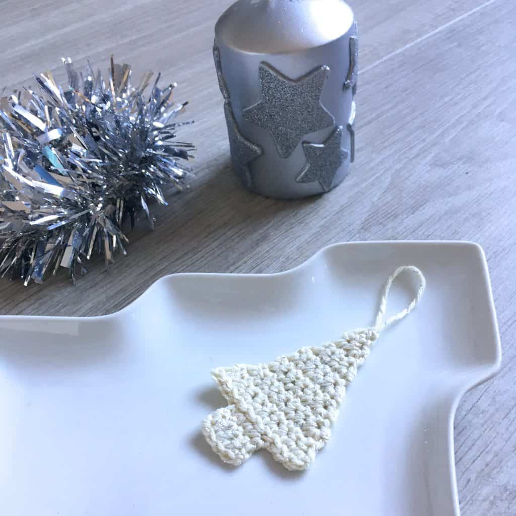 crochet christamstree decoration on tree shaped plate with candle and tinsel