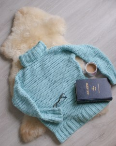 Cosy Crochet Sweater with cuppa book glasses on sheep pelt