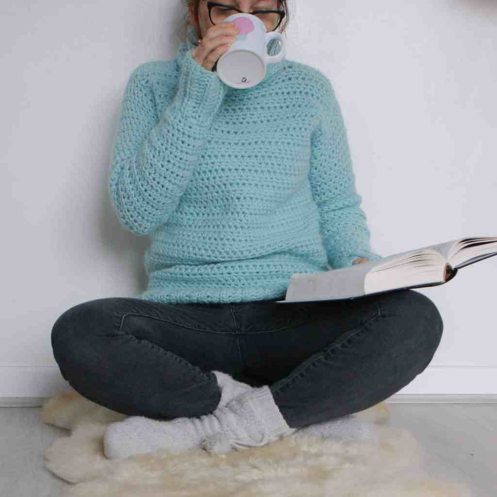 Woman reading drinking tea in cosy crochet sweater