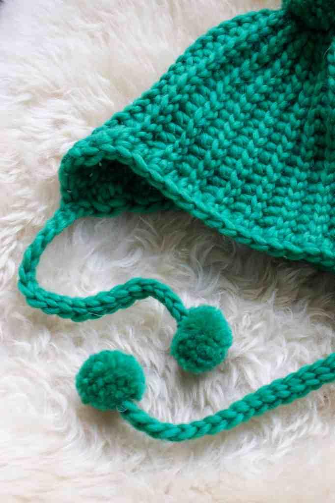 Green crochet hat with pom pom tassels