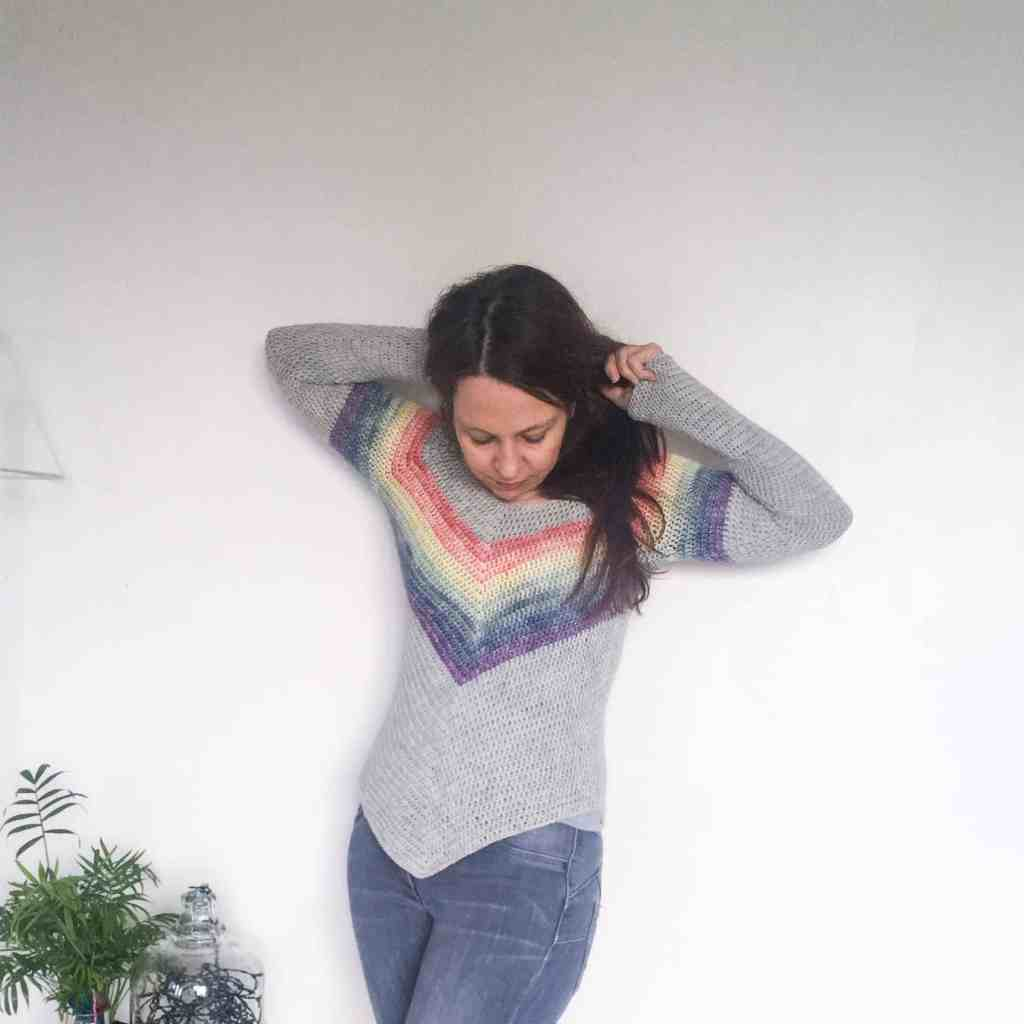 Woman wearing rainbow crochet sweater holding hair