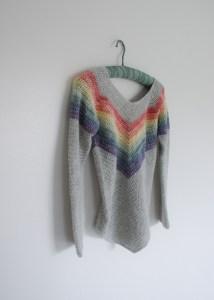 Crochet Rainbow Sweater hanging on white wall