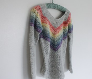 Crochet Rainbow Sweater hanging on white wall
