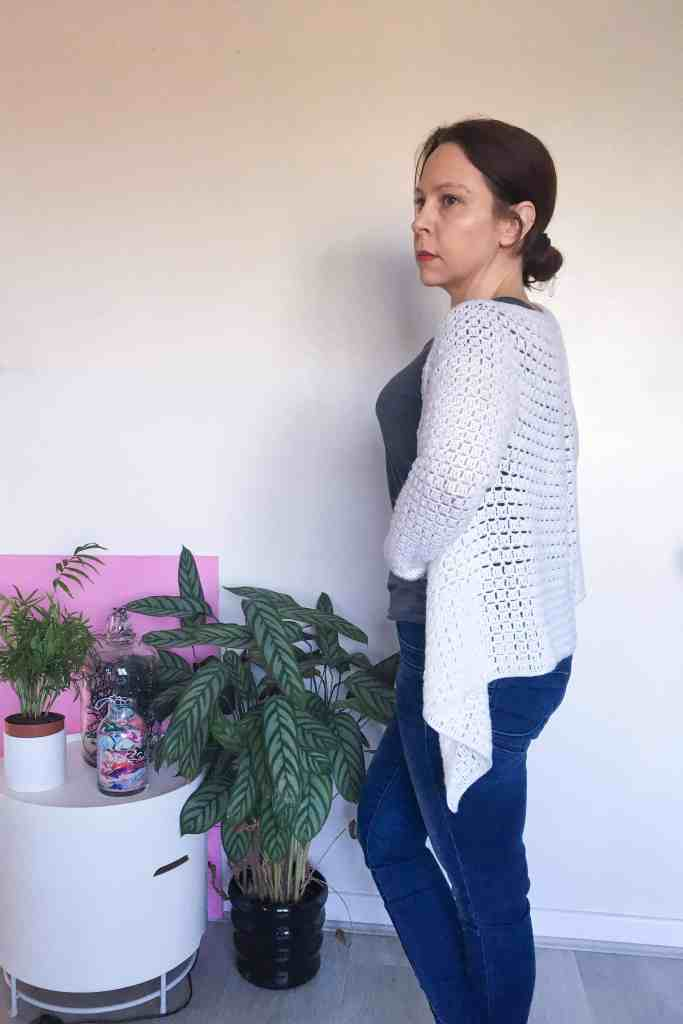Woman in front of white wall wearing white crochet cardigan