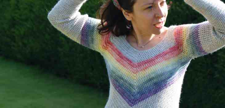 Woman in rainbow chevron crochet sweater in country garden