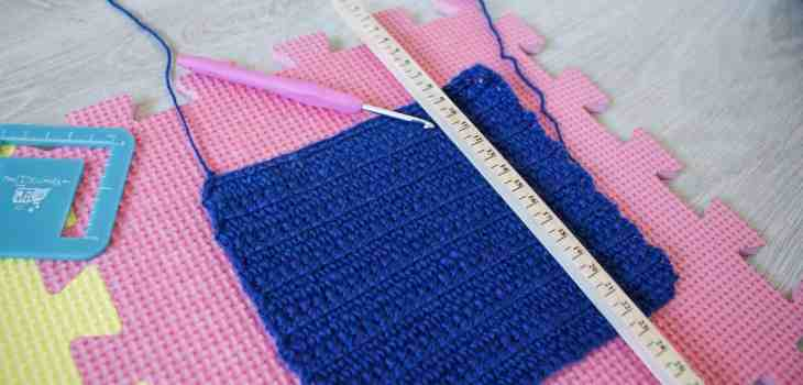 Ruler measuring rows on crochet swatch with hook