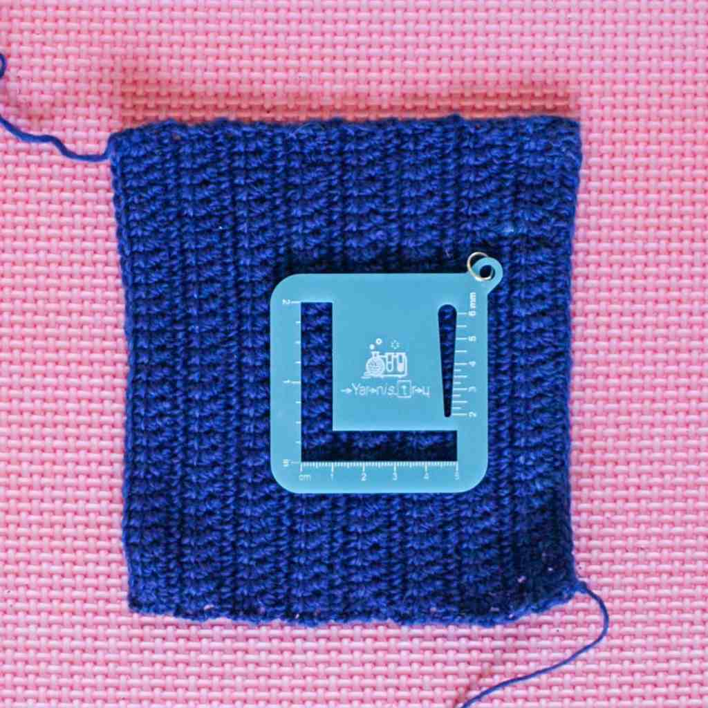 Blue crochet gauge swatch with gauge measure on pink blocking mat