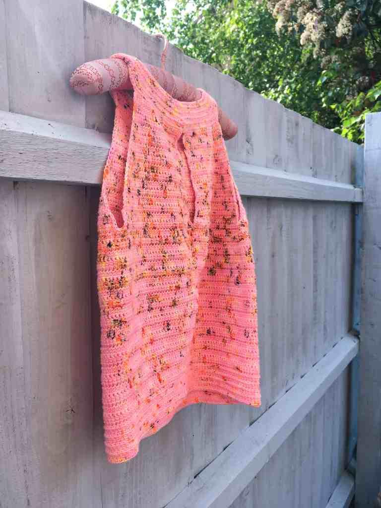 Pink keyhole back crochet summer top hanging on a blue grey fence