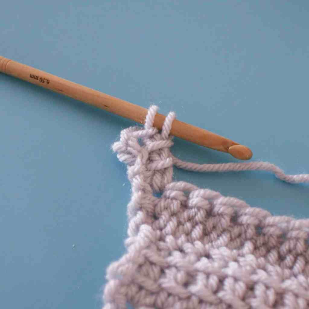Crochet tutorial step grey yarn swatch on blue background being worked with wooden crochet hook