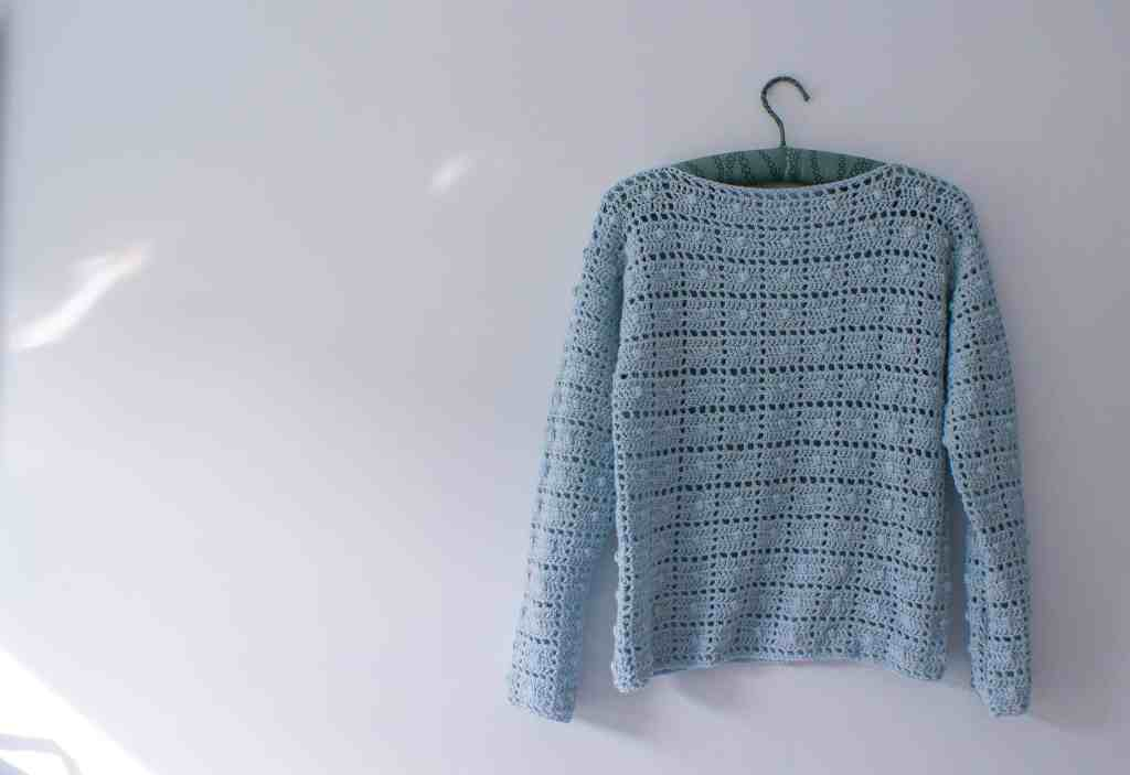 blue geometric bobble crochet sweater hanging on white wall