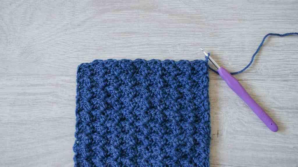 Blue crochet swatch, purple crochet hook on grey wool effect floor