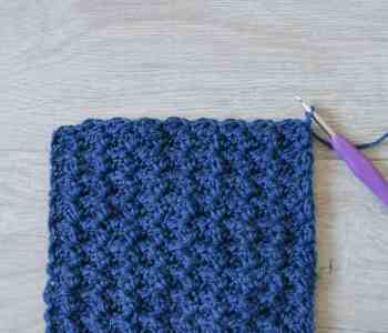 Blue crochet swatch, purple crochet hook on grey wool effect floor