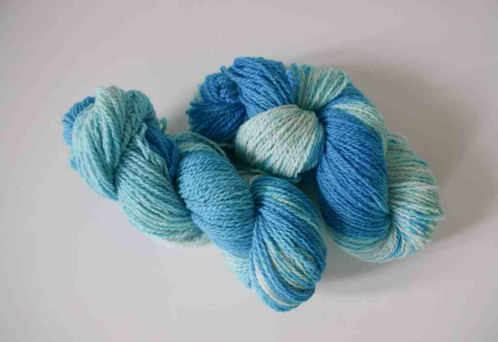 two skeins of yarn hand dyed with blue food colouring